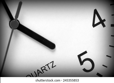 Close up of a modern clock face in black and white with the hour hand pointing at five o'clock. A vignette has been added to the image for effect