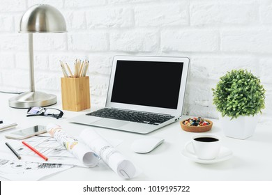 Close up of modern designer desk with blank laptop, smartphone, supplies and other items. White brick wall background. Web design concept. Mock up