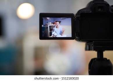 Close up of modern digital camera shooting video blog of young lady. Focus on camcorder with beauty blogger on display