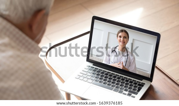 Close up of modern elderly man sit at home having online consultation with doctor on computer, sick senior male talk on video call consulting with female nurse using laptop, healthcare concept