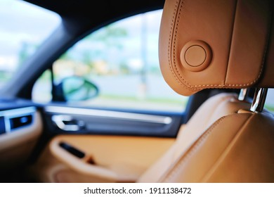 Close up of modern luxury brown car leather passenger seat with blurred sedan interior components and window view of outside. Vehicle industry design element. Detail of leather auto headrest texture.