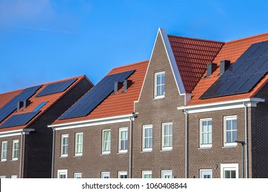 Close up of Modern row houses with solar panels, brown bricks and red roof tiles in neoclassical style in Groningen Netherlands