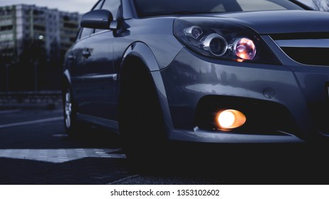 Close up of modern sedan headlamp. Front view shot from side of vehicle. Car headlight background.
