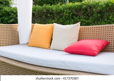 Close up modern sofa  wicker and color pillows in the garden.