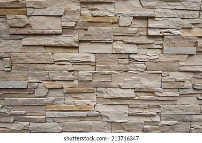 Close up of modern style design decorative uneven cracked real stone wall surface with cement