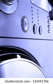 Close up of a modern washing machine control panel, with timer and options low key blue tone
