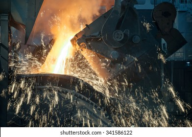 close up of  molten metal pouring from ladle into mould