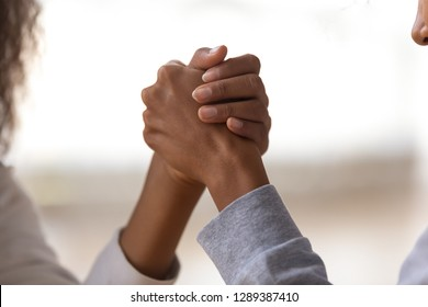 Close up of mom and daughter holding hands showing unity, support and understanding, African American female friends play funny wrestle game, mother or nanny and child unity concept