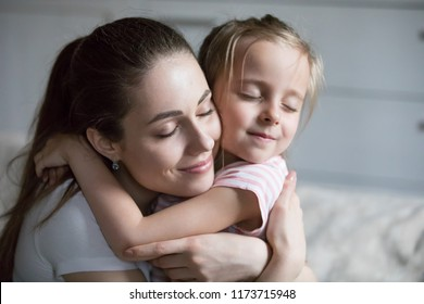 Close up of mom hug daughter showing love and support, caring young mother embrace girl enjoying sweet moment together, happy parent hold in arms cute little child make peace or reconcile after fight