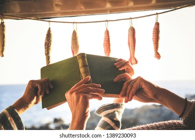 Close up of mom and son hands reading a book together lying in the camper in the light of sunset. Concept of family and quality time sharing. Mother and daughter studying on vacation. Home schooling.