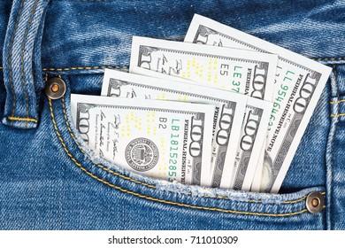 Close up money in pocket of blue jean. One hundred dollar bills in back of jean pocket.