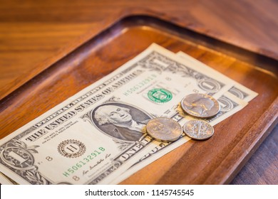 Close up money in wooden tray on cafe's table, dollar banknotes and US coins, modern and minimal style. Concepts for Bill received, fee charge, customer service, checking, money tips.