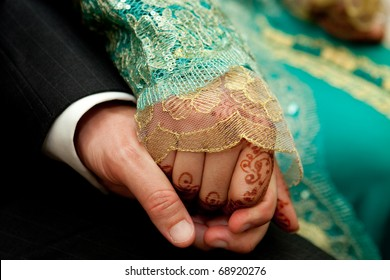 close up of moroccan bride's hand holding groom's hand