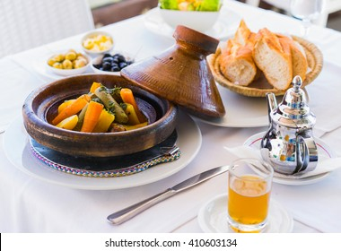 Close up moroccan food: tajine, mint tea, olive and bread.  Focus on tajine.