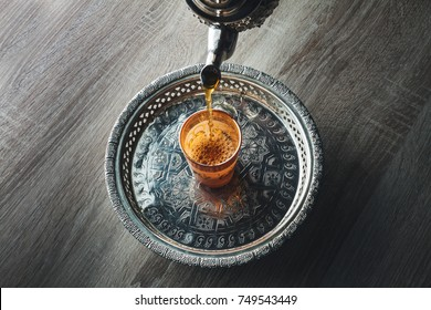 close up of moroccan traditional tea pot and glass on a silver plate