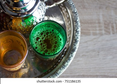 close up of moroccan traditional teapot  and a cups of tea on a silver tray