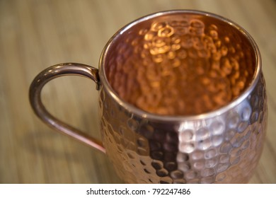 Close up of moscow mule copper mug cup cocktail on wood cutting board angle shot of handle