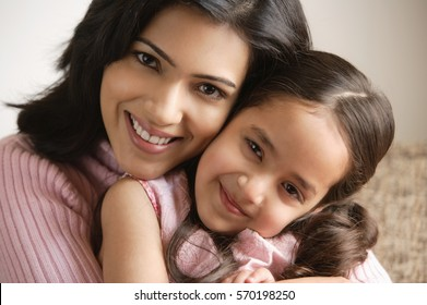 close up of mother and daughter hugging and smiling at camera