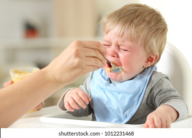 Close up of a mother hand feeding his son who is crying sitting on a high chair