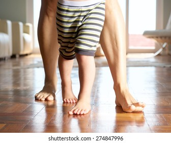 Close up mother and little boy walking on wood floor at home