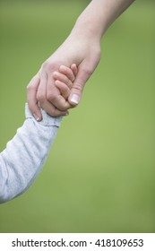 Close up of Mother and son holding hands outdoors. Parenthood, Love and togetherness concept.