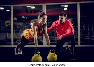 Close up of motivated focused attractive young woman doing push ups exercise on the kettlebells in the gym with her handsome muscular personal trainer.