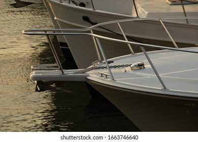 Close up of motor yachts bow and anchor moored at Marina at sunset