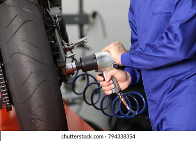 Close up of a motorcycle mechanic hands working usinb a pneumatic gun to thighten a nut in a mechanical workshop