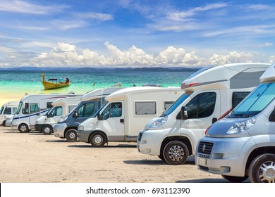 Close up motorhomes parked in a row on white sand beach and blue sky background.