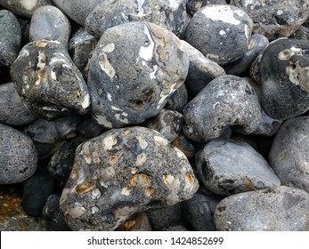 Close up of mound of grey stone large rock pebble stones with pattern flint white different shapes smoothed by the sea on shore of the ocean beach outside environment in day light on cold bright day