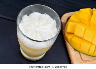 Close up of mousse of mango fruit with whipped cream in a glass jar and mango cubes on a table