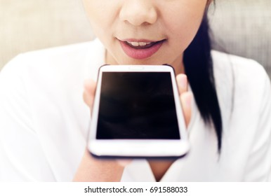 Close up of mouth business girl using a smart phone voice recognition with a warm light background.
