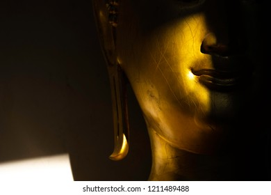 close up mouth and face golden buddha statue in the light and shadow of sun at Wat Pra Sri Mahathat temple, Phitsanulok province, Thailand