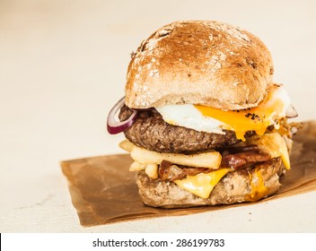 Close up Mouth Watering Homemade Burger with Patty, Cheese, Onion Rings and Fries on Top of a Brown Paper, Isolated on beige Background.