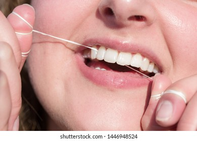 close up of a mouth of a young woman flossing her teeth