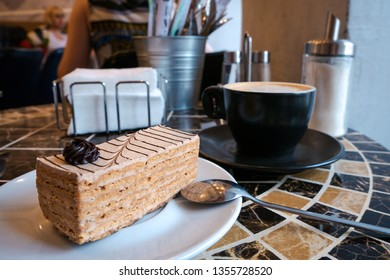 Close up of mouth-watering piece of layered cake with brown rose decoration on white plate with spoon and coffee in black cup and saucer