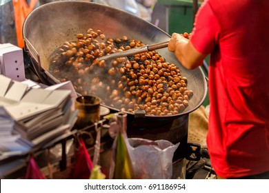 Close up movement hand a man worker roasting chestnuts in street chinatown or Yaowarat Road in Bangkok, Thailand