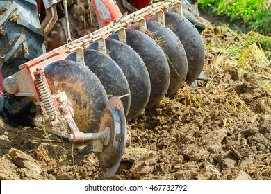Close up moving ploughs in field when farmer plowing with tractor make soil, straw and grass up prepare agricultural area for planting.