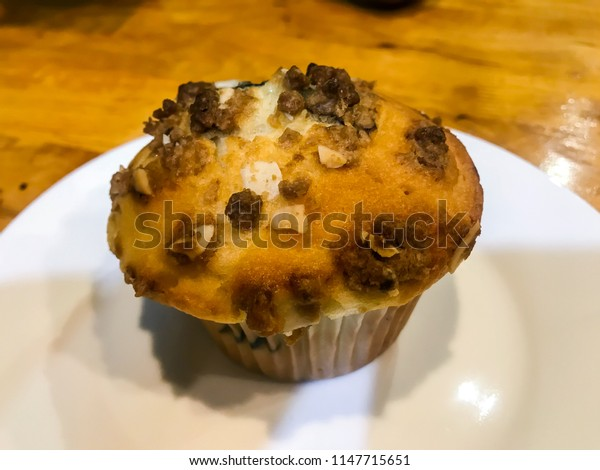 Close up muffin and orange cheese cake on white dish with wooden table background