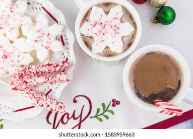 Close up of mugs of  hot chocolate and plate with marshmallows topping, peppermint stirrers on table decorated for Christmas.