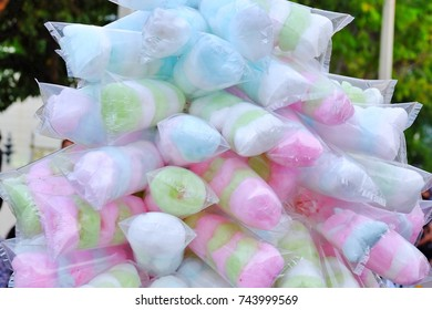 Close up a multicolored of cotton candy in a plastic packaging and a merchant selling on a street in the outdoor festival