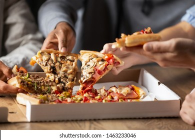 Close up of multiethnic young people gather in pizzeria together have fun sharing tasty Italian food, diverse colleagues or friends take pizza slices enjoy dining out in bar, takeaway delivery service