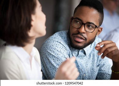 Close up of multiracial colleagues chat talking or discussing something in office, black man speak with female coworker negotiating about business project, having conversation. Cooperation concept