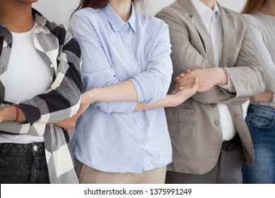 Close up multiracial group of people with arms twisted. Young milennial man and women hold each other hand in row. Friendship, support, team, team work, team building, human resources, hr concept