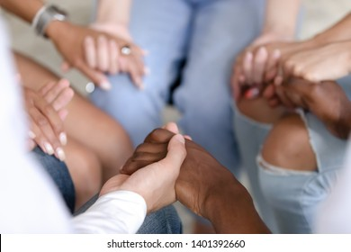 Close up of multiracial people sit in circle holding hands show mutual support and understanding at therapy session, diverse men and women gather give help at group psychological treatment