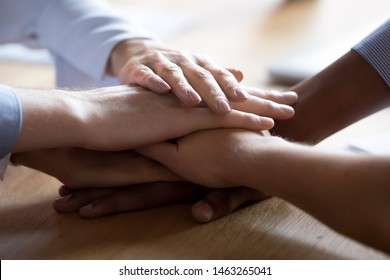 Close up of multiracial people stack join hands on wooden desk show integrity and support at work, diverse colleagues or employees engaged in teambuilding activity express unity and team spirit