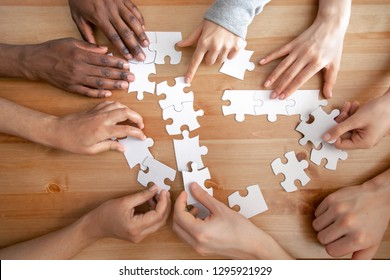 Close up multiracial people, team assembling puzzle, success teamwork and teambuilding concept, students or colleagues finding best creative solution, decision together, hands top view