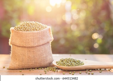 Close up of mung beans in small wooden sack on wooden table. Outdoor shooting with sunlight and green blur bokeh and lens flare effect background