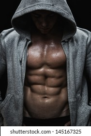 Close up of muscular sports man after weights training over black background