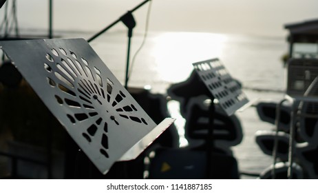 Close up Music stand with blurred Microphone Stand and Equipment on stage against sun light on sea Background. Outdoor mini concert concept.